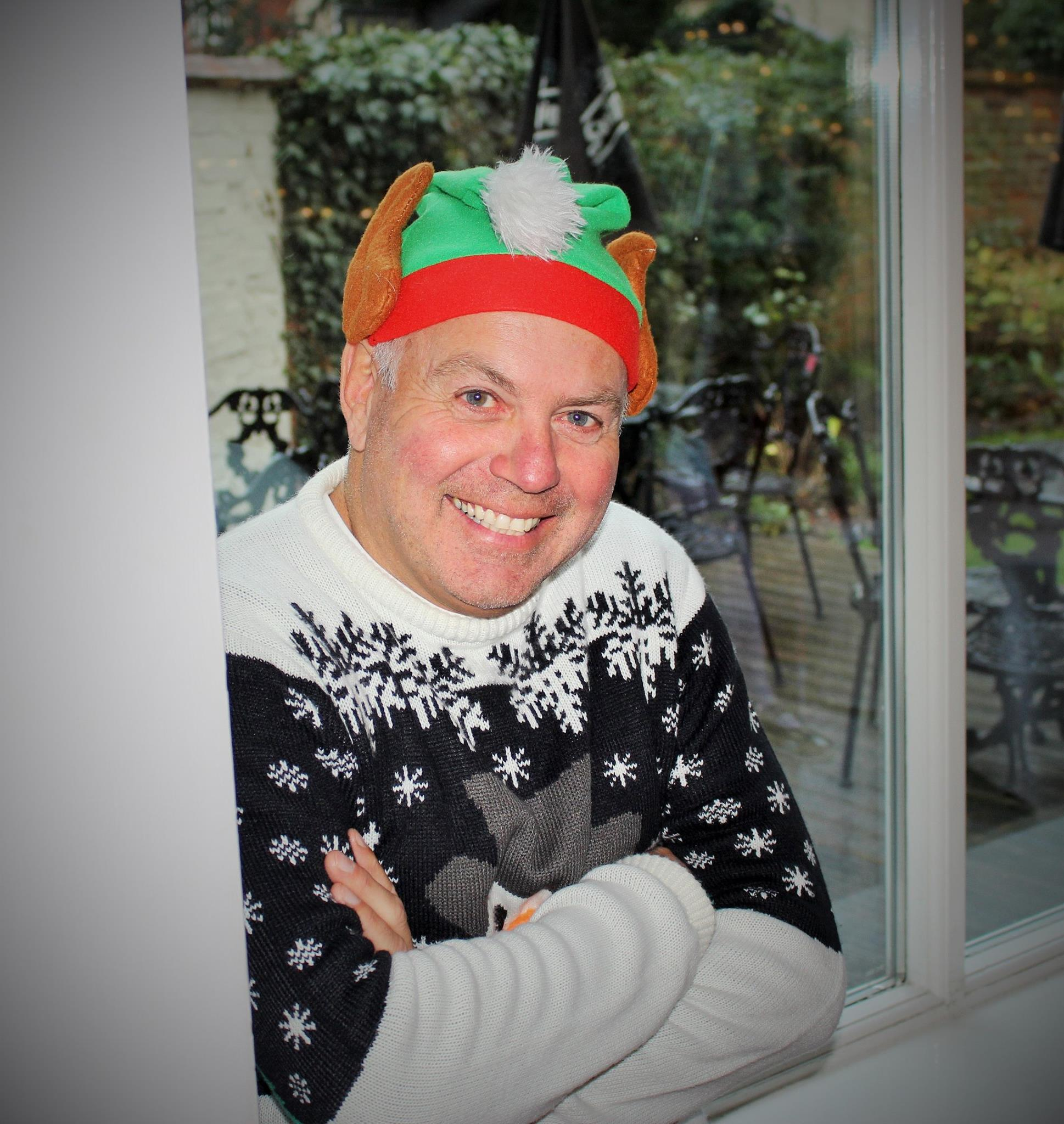 An older man smiling at the camera and wearing a Christmas jumper and a festive 'turkey' hat