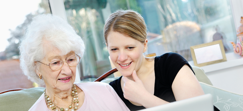 older woman being taught how to use a computer by younger woman