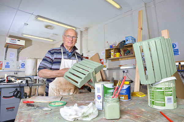 Older man painting trug