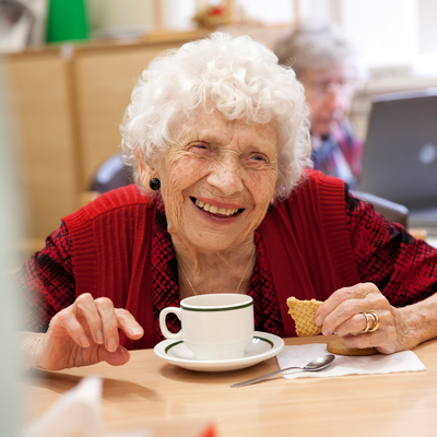Woman eating tea & biscuits