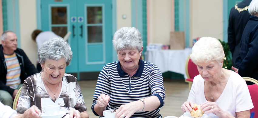Three ladies sitting at a table enjoying tea and cake