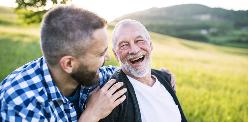 An older man out sharing a moment of humour with his male carer