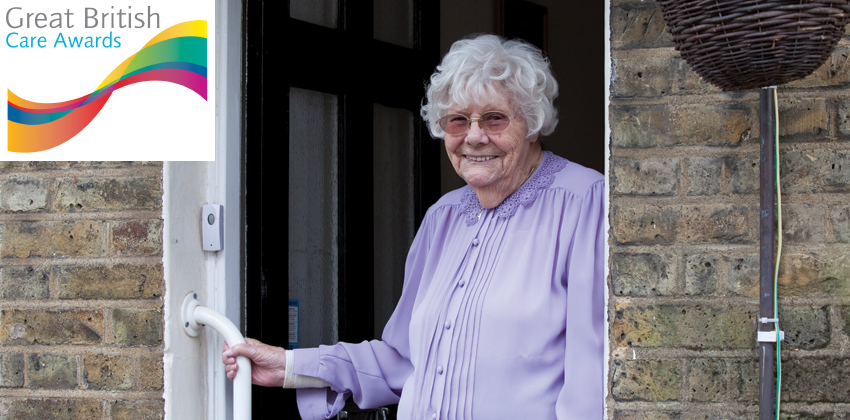 An older woman standing smiling in the doorway to her house