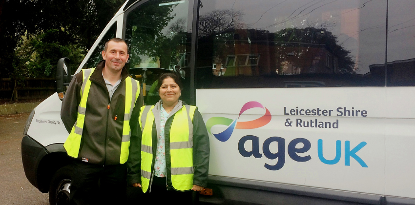 Two of our Minibus Drivers standing and smiling in front of one of our minibuses