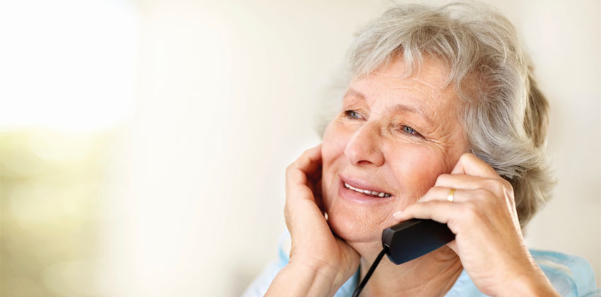 An older woman talking on the telephone