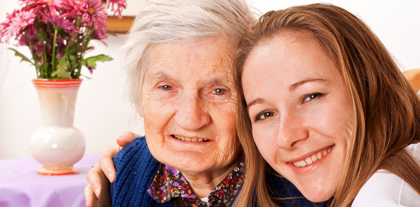 An older lady sitting with a carer