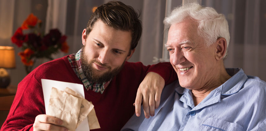 Younger man going through old letters and memories with an older man