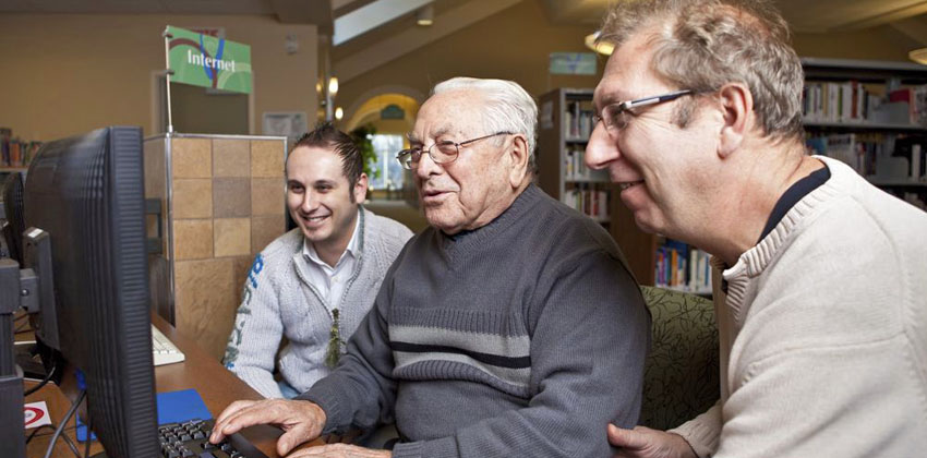 An older man being shown how to make the most of a computer