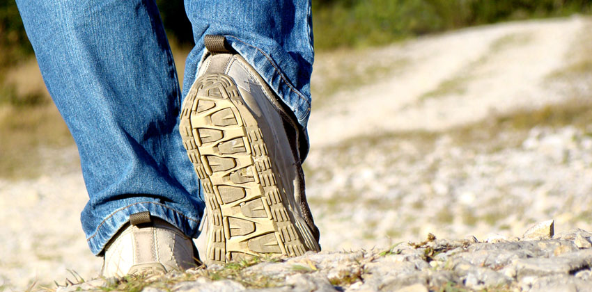 A close-up of someone wearing walking shoes over rocky terrain