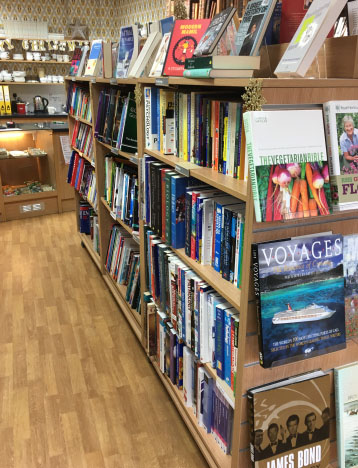 The inside of our Queens Road Bookshop with lots of lovely books on display and the cafe in the background
