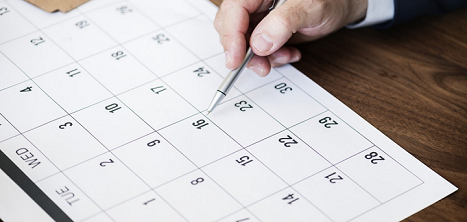 A hand filling in a calendar - your priorities