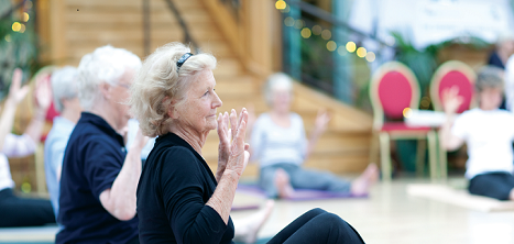 An older woman takes part in an exercise class.