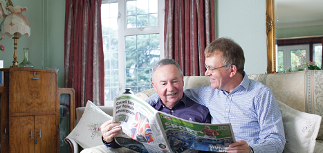 Two older men sat on the sofa reading the paper together. The man on the right has his arm around the man on the left.