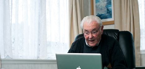 An older man using a laptop at home.