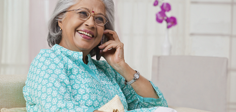 An older lady talks happily on the phone.