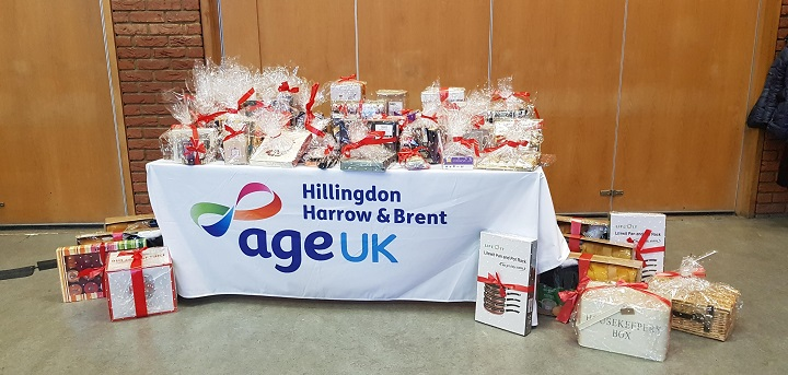 A photo of a table bearing gifts. The Age UK Hillingdon Harrow and Brent logo appears on the tablecloth
