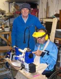 Two men hard at work operating a lathe at the shed.