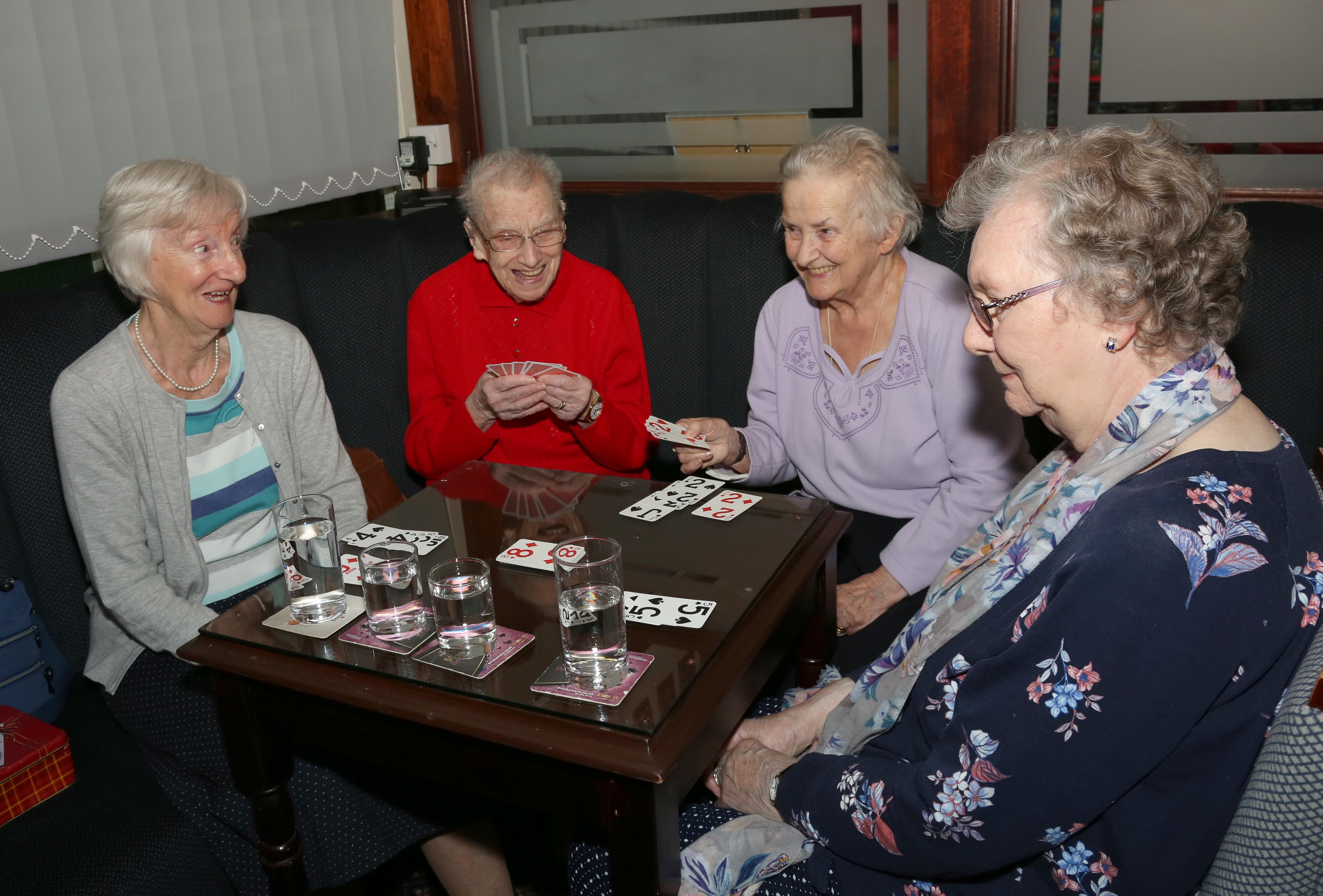 4 people playing cards round a table