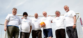 Group of older men playing football