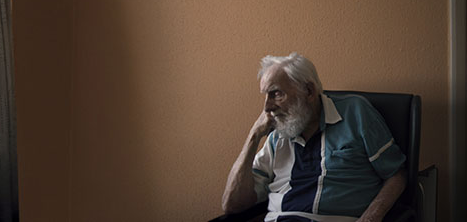 An older man sits in an armchair, looking pensive