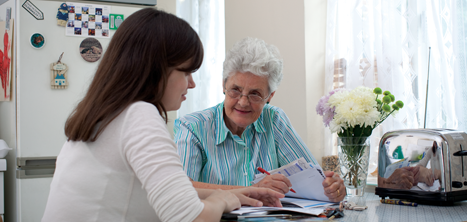 An older woman and a volunteer discussing paperwork