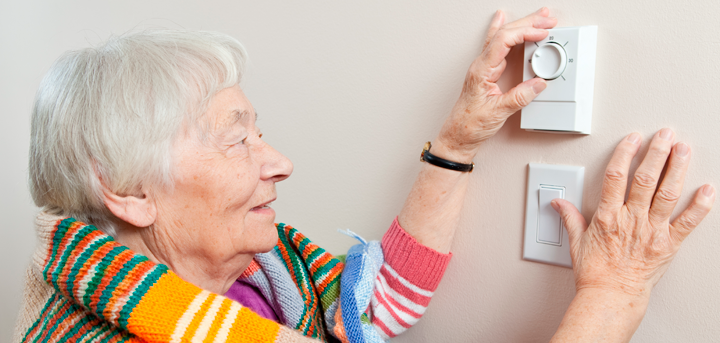 Older woman adjusting a thermostat