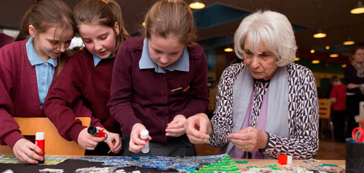 An older woman working with schoolchildren on an art project