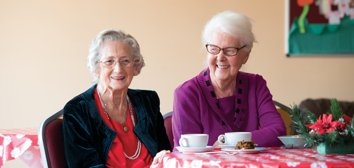 Two older women enjoying tea at a social group