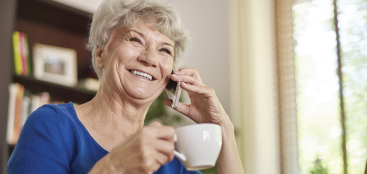 An older woman enjoying a phone call from a befriender