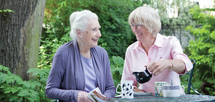 An older woman and a volunteer befriender enjoying a cup of tea together