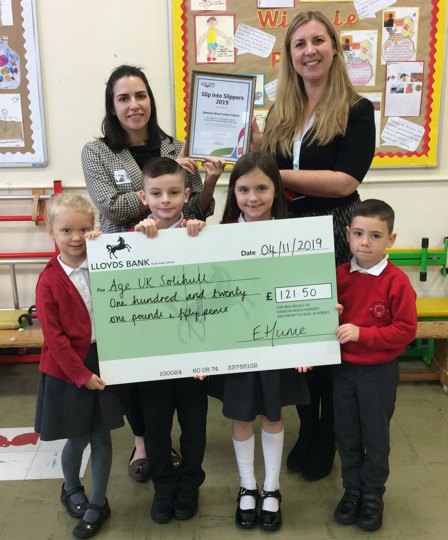 Fundraising Officer, Becky, and Damson Wood Infant School Headteacher, Mrs Hume, holding a certificate, and four children from the school holding a giant cheque.