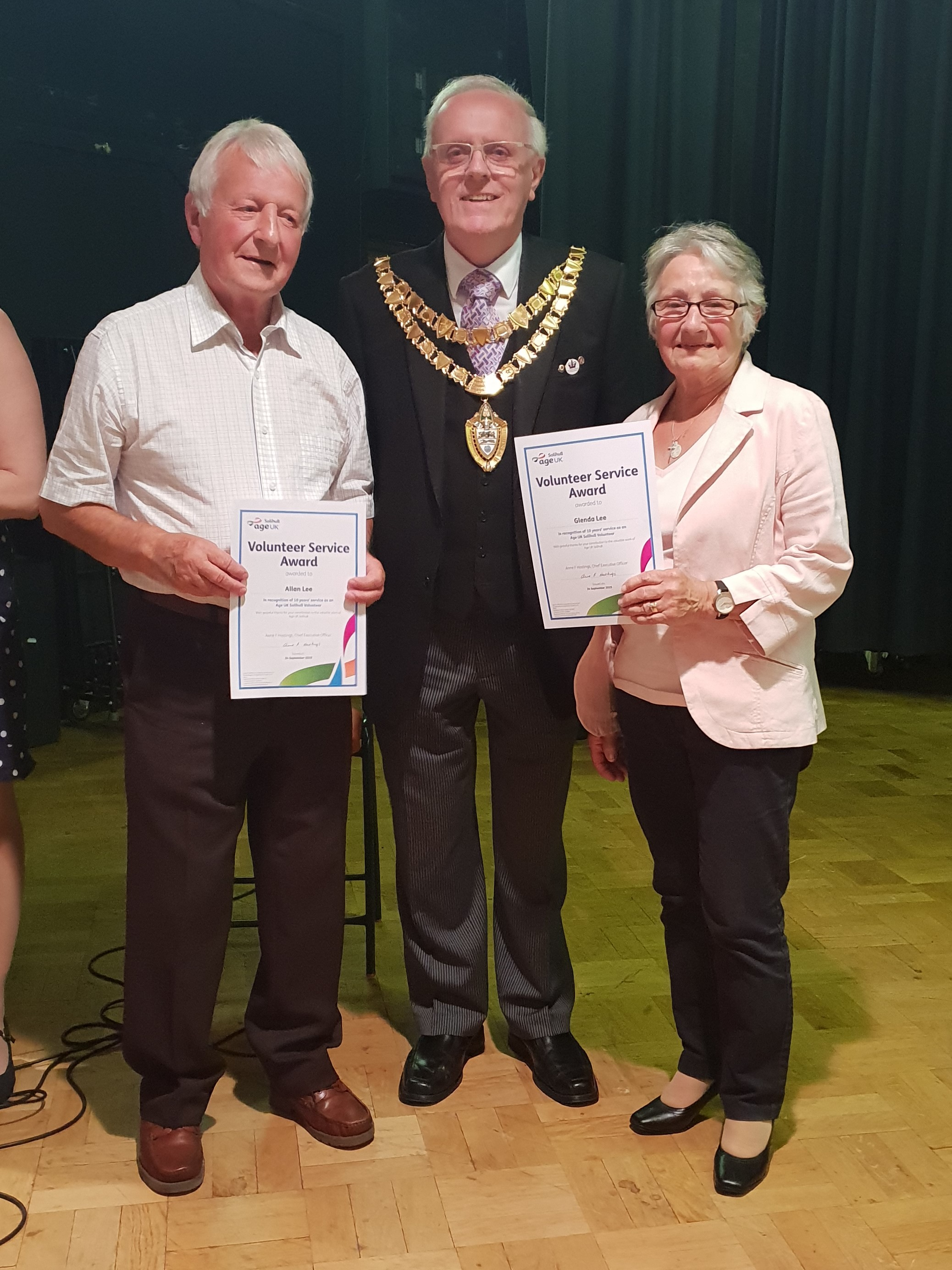 Two people standing next either side of the Mayor of Solihull, holding certificates to mark 10 years' volunteering for Age UK Solihull