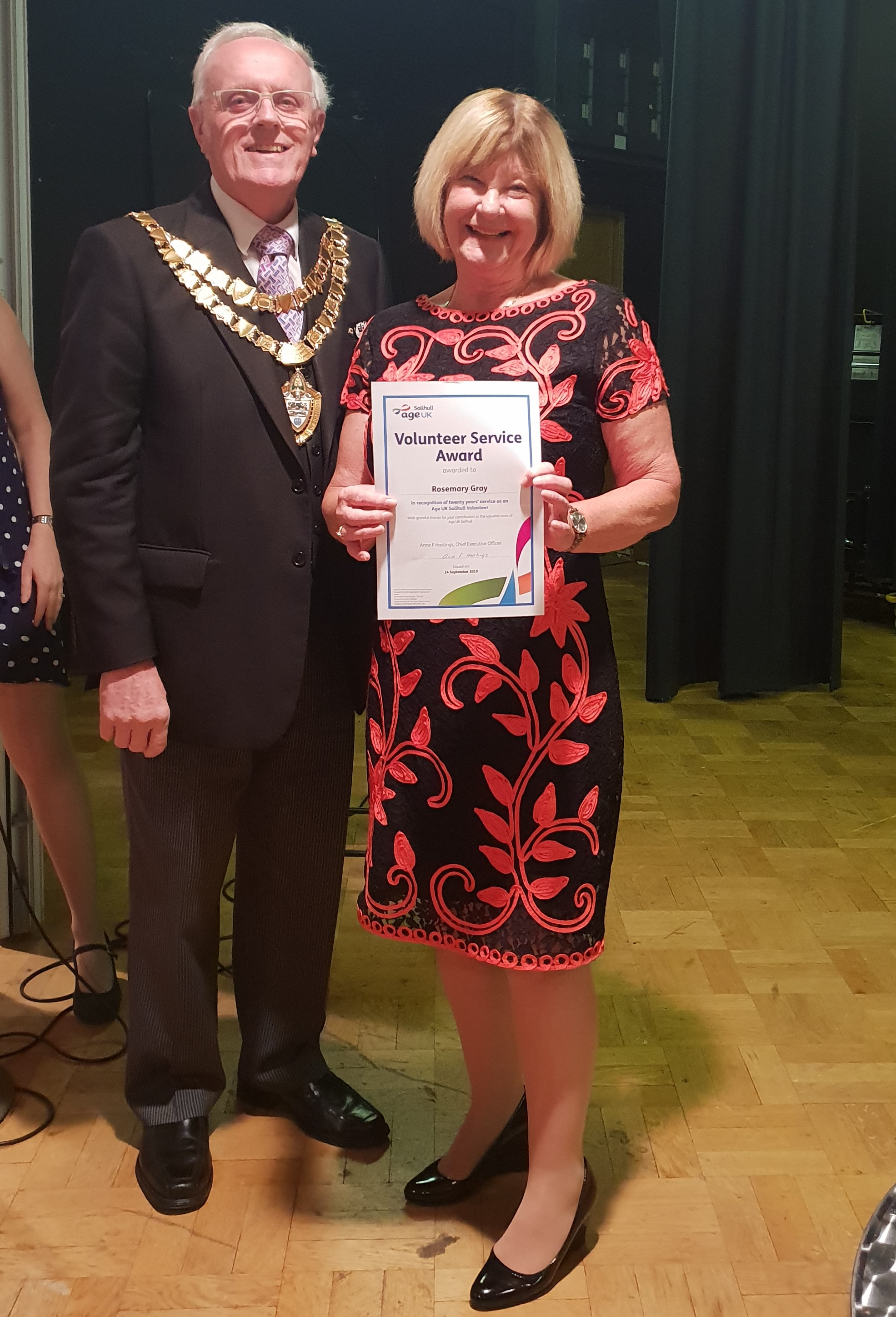 Mayor of Solihull stands with Rosemary Gray, who is wearing a black and red dress and holding a certificate for 20 years' service as an Age UK Solihull volunteer.