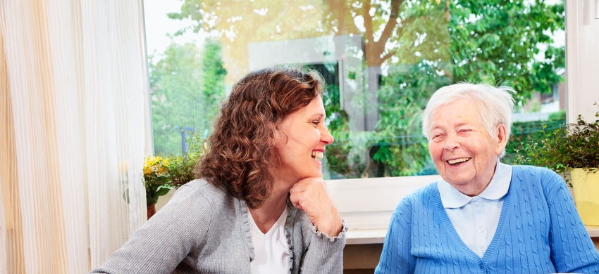 younger woman laughing with older woman at home