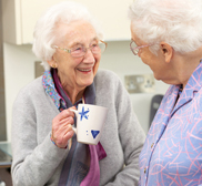 two ladies chatting with a cup of tea