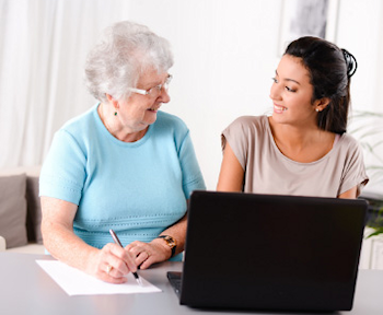 photo of younger woman helping older woman on PC