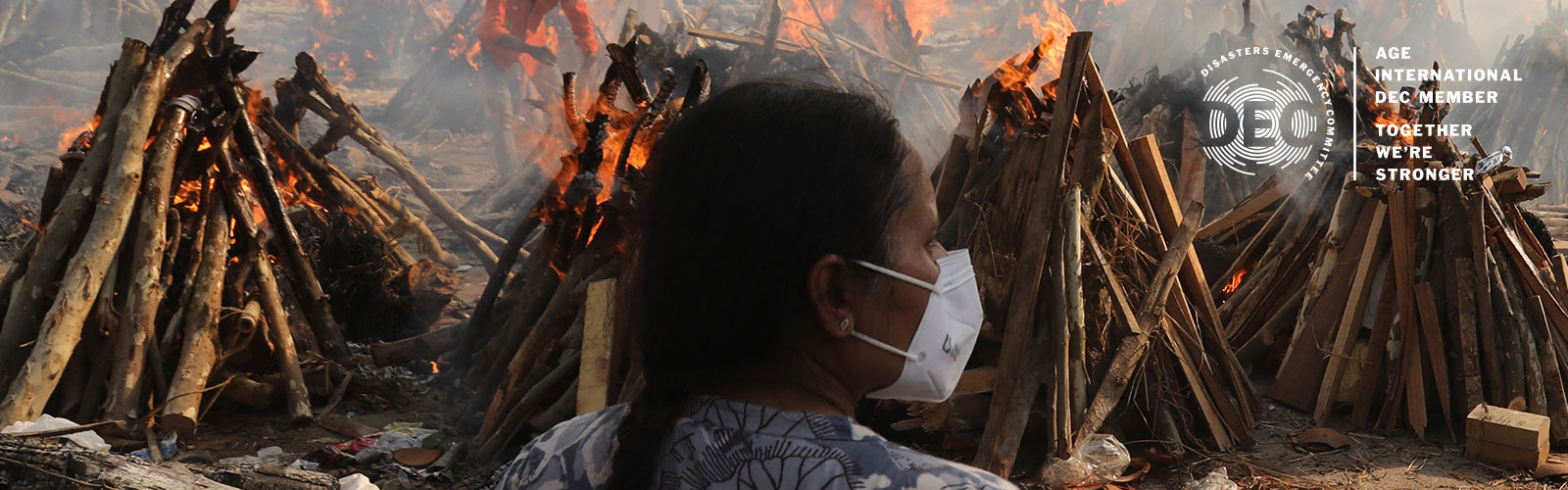 A woman looks at the burning bodies of those who have died from coronavirus in India