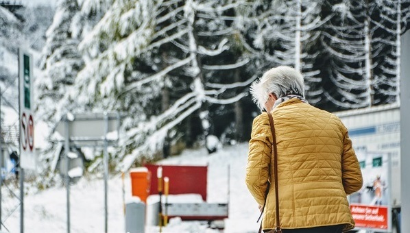 Older woman walking in the snow