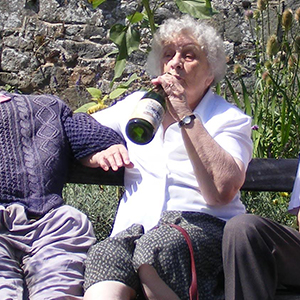 A woman sits on a bench and jokingly drinks from a bottle of champagne