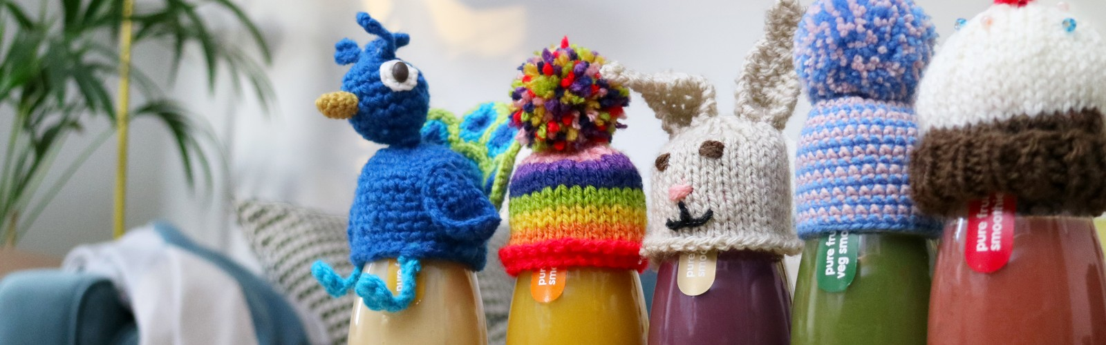 A collection of little hats on top of innocent smoothie bottles