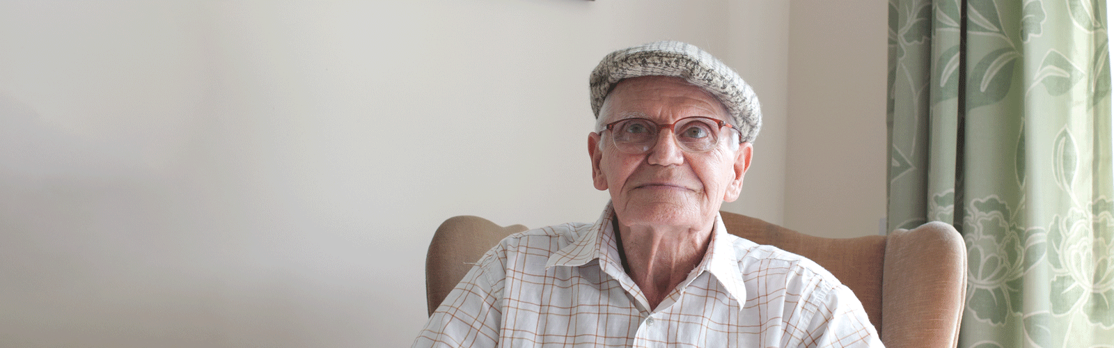 Man in glasses and flat cap sitting in armchair and looking at camera