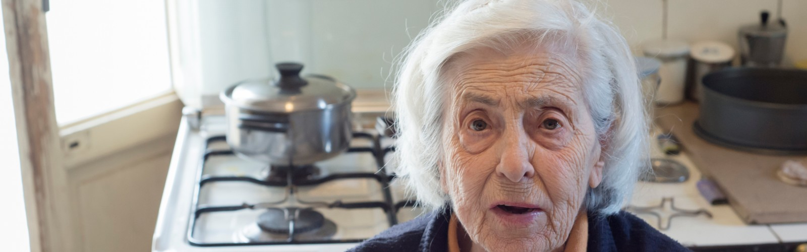 An older woman sits in her kitchen, looking concerned