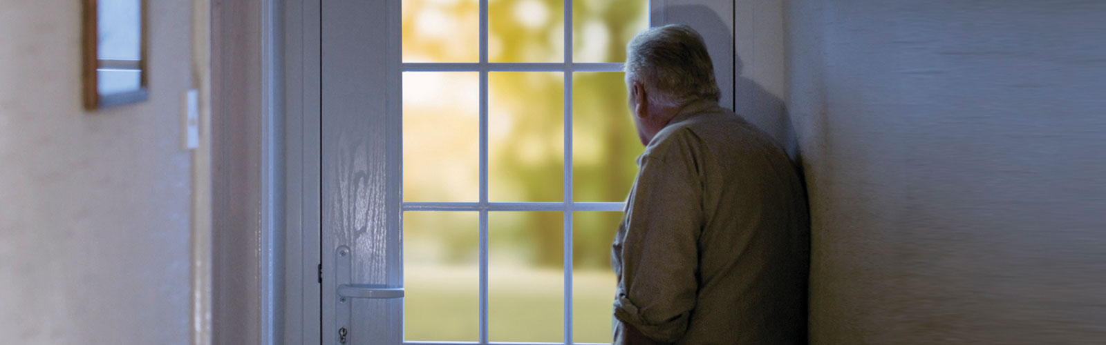An older man with his back to the camera looks out of his  window longingly