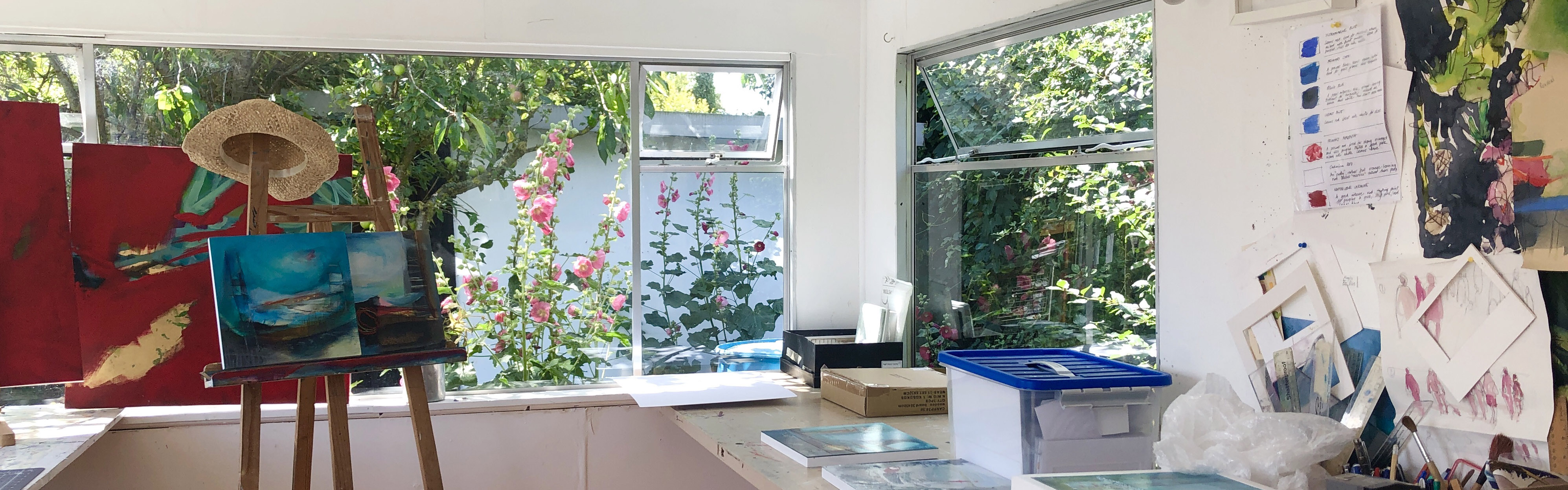 An image of an easel next to a window opening out onto a garden full of pink flowers