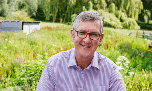 Keith Oliver, author of Dear Dementia, smiles at the camera with a green garden and wild flowers behind him