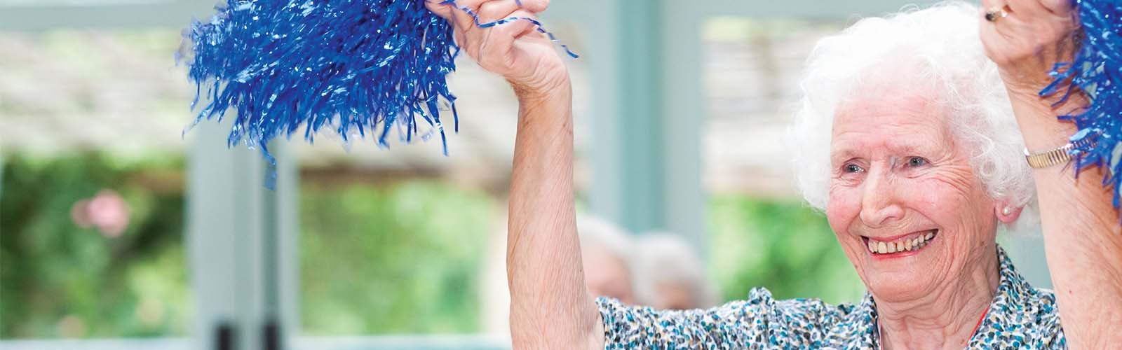 An older lady waves cheerleading pompoms at an Age UK activity class