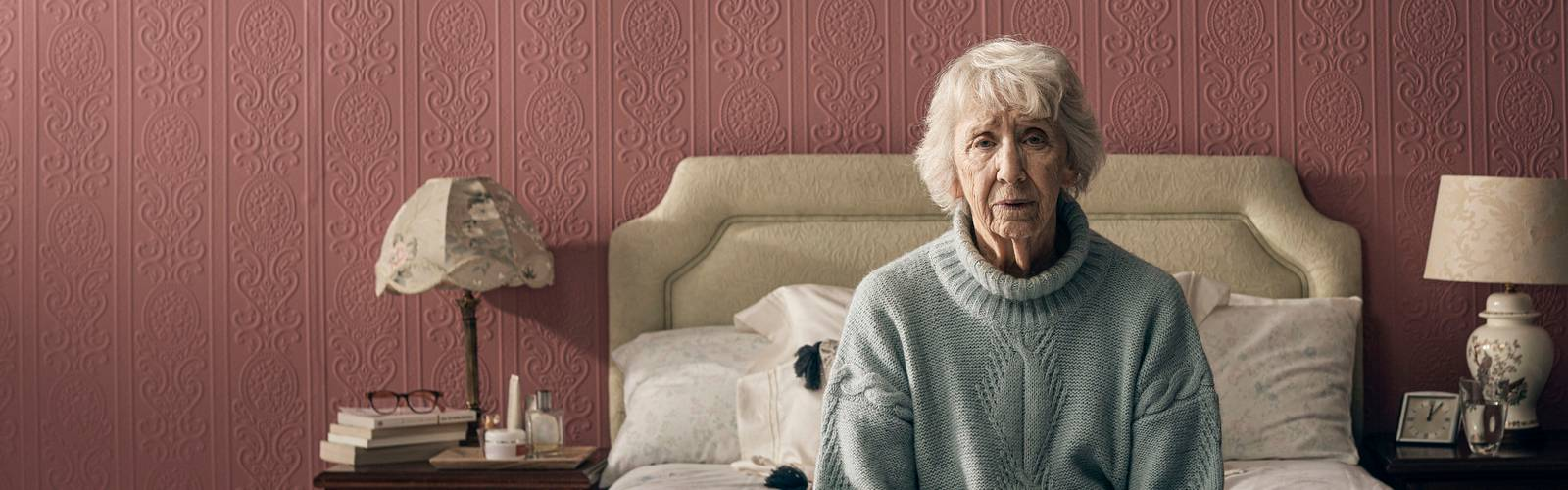 An older woman sits alone on her bed, looking worried