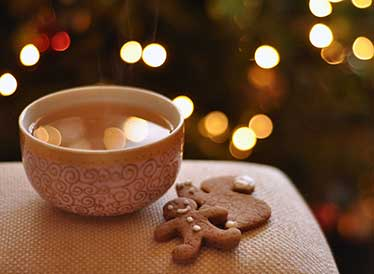 Hot tea and gingerbread biscuit with fairy lights in the background