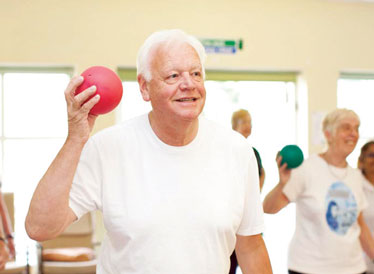 Man holding a red ball at an exercise class