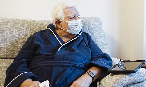 An older man sat on a sofa, wearing a face mask